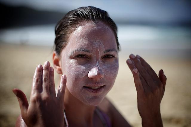 Femme qui se met de la crème solaire sur le visage.