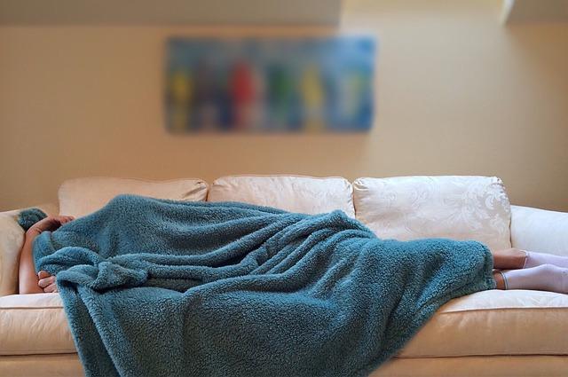 Une personne fait la sieste sur un canapé.