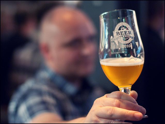Un homme tenant un verre de bière.