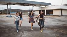Groupe d'adolescentes marchant et rigolant ensemble.