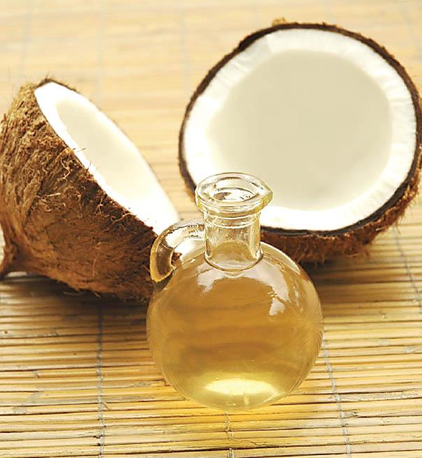 Fiole d'huile de noix de coco, devant une noix de coco fendue.