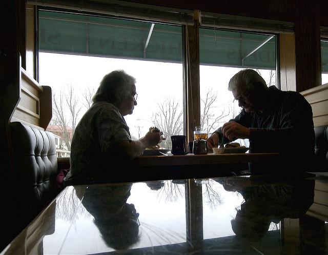 Couple de personnes âgées déjeunant au restaurant.