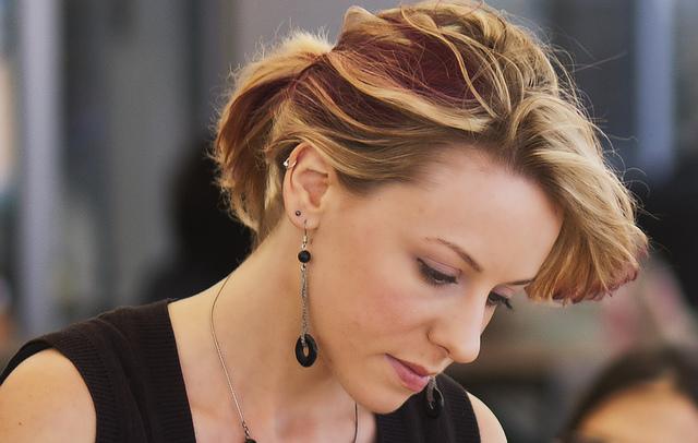 Photographie d'une femme blonde avec les cheveux attachés.