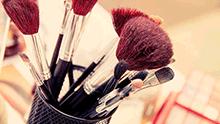 Des pinceaux de maquillage dans un pot.
