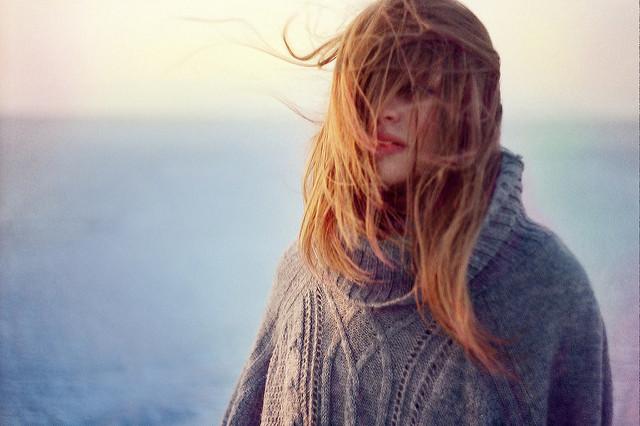Femme les cheveux au vent et emmitouflée dans un pull.