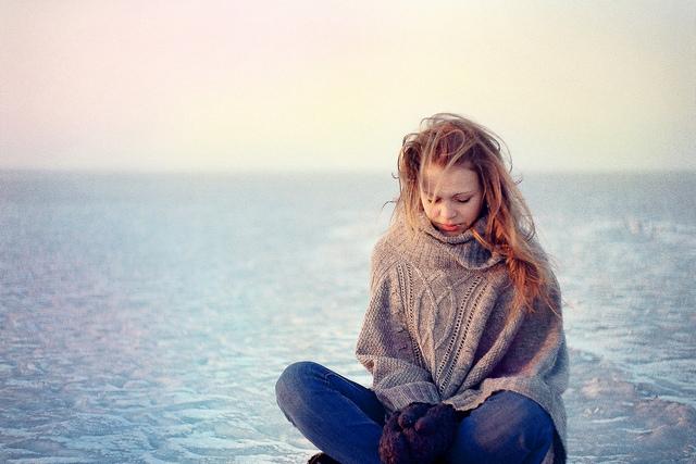 Jeune femme en bord de mer, emmitouflée dans un poncho en laine et de grosses mouffles.