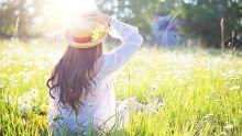 Jeune femme de dos assise dans l'herbe au printemps.