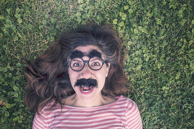 Jeune femme déguisée avec des gros sourcils et une moustache.