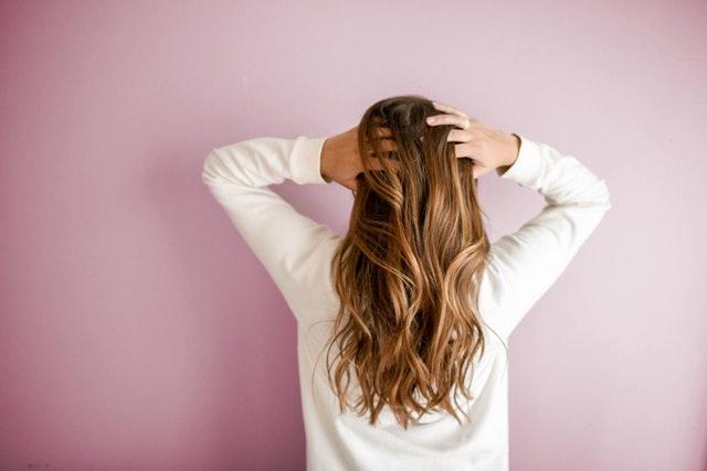 Une femme de dos qui se touche les cheveux.