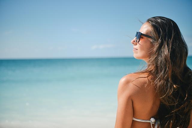 Femme de dos, le visage de profil, sur une plage en été.