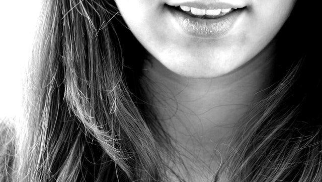 Sourire d'une jeune femme qui a une bonne santé bucco-dentaire.