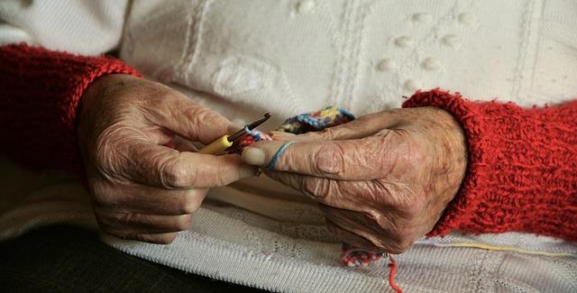 Mains de personne âgée en train de tricoter.