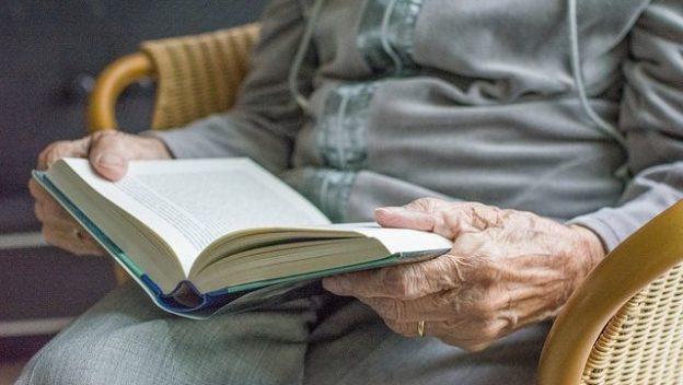 Personne âgée en train de lire un livre en maison de retraite.