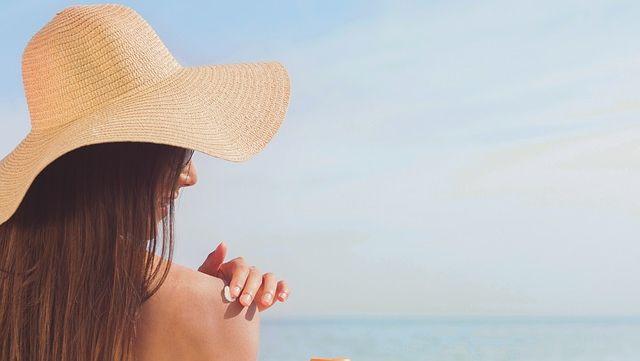 Une femme s'étale de la crème solaire.