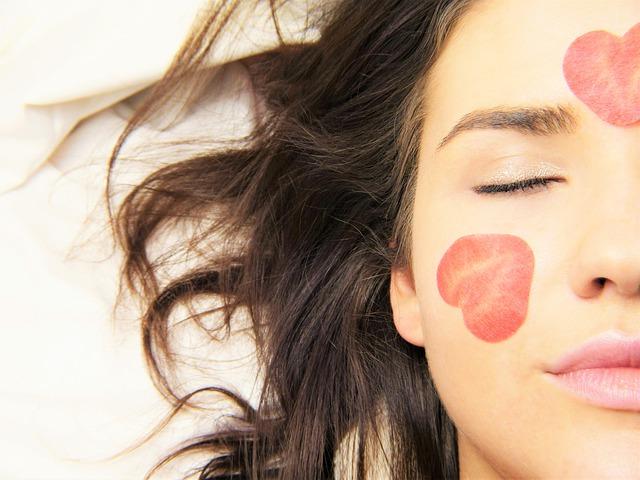 Jeune femme avec un masque de fraise sur le visage.