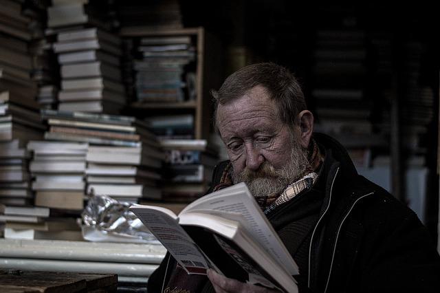 Une personne âgée qui lit au milieu d'un tas de livres.