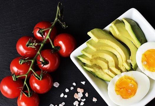C'est une assiette avec des avocat, des œufs ainsi que des tomates cerises.