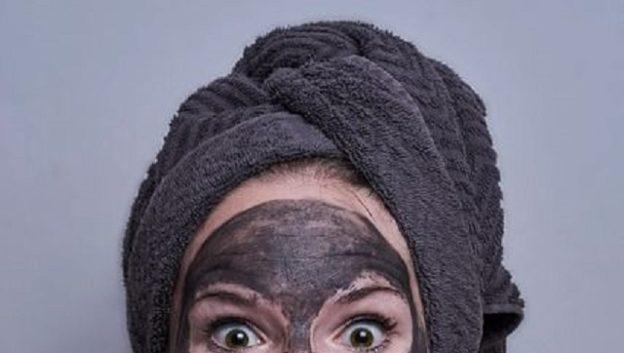 C'est une femme surprise qui a un masque de beauté sur le visage.