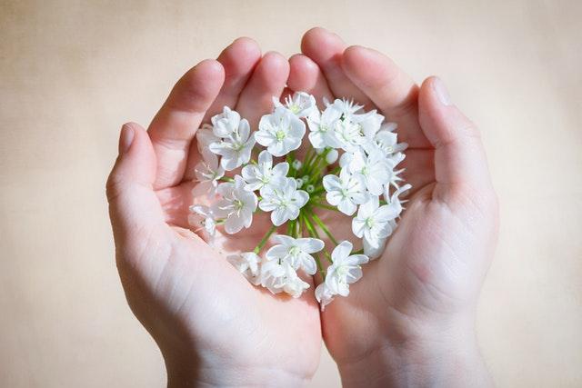 Mains qui tiennent des fleurs.