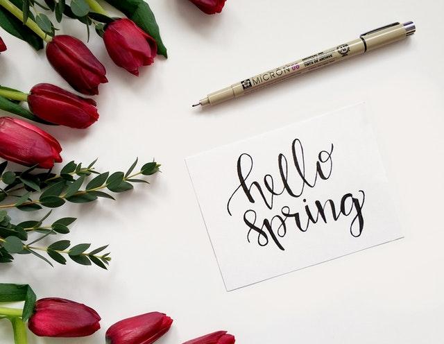 """Tulipes rouges autour d'une carte avec l'inscription """"Hello Spring""""."""
