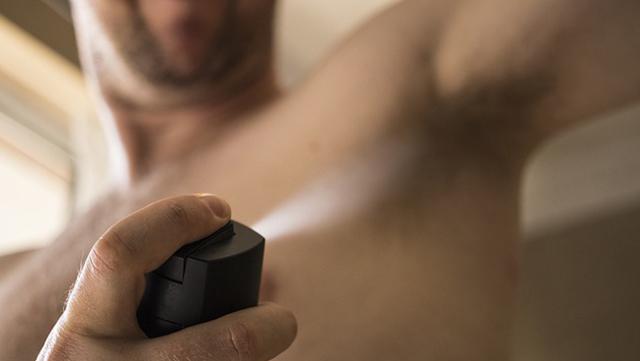 Homme se mettant du déodorant