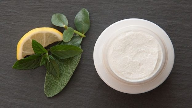 Crème bio posés à côté de fruits