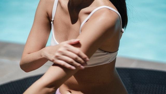 Femme appliquant crème solaire