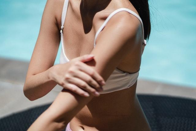 Femme se passant de la crème solaire.